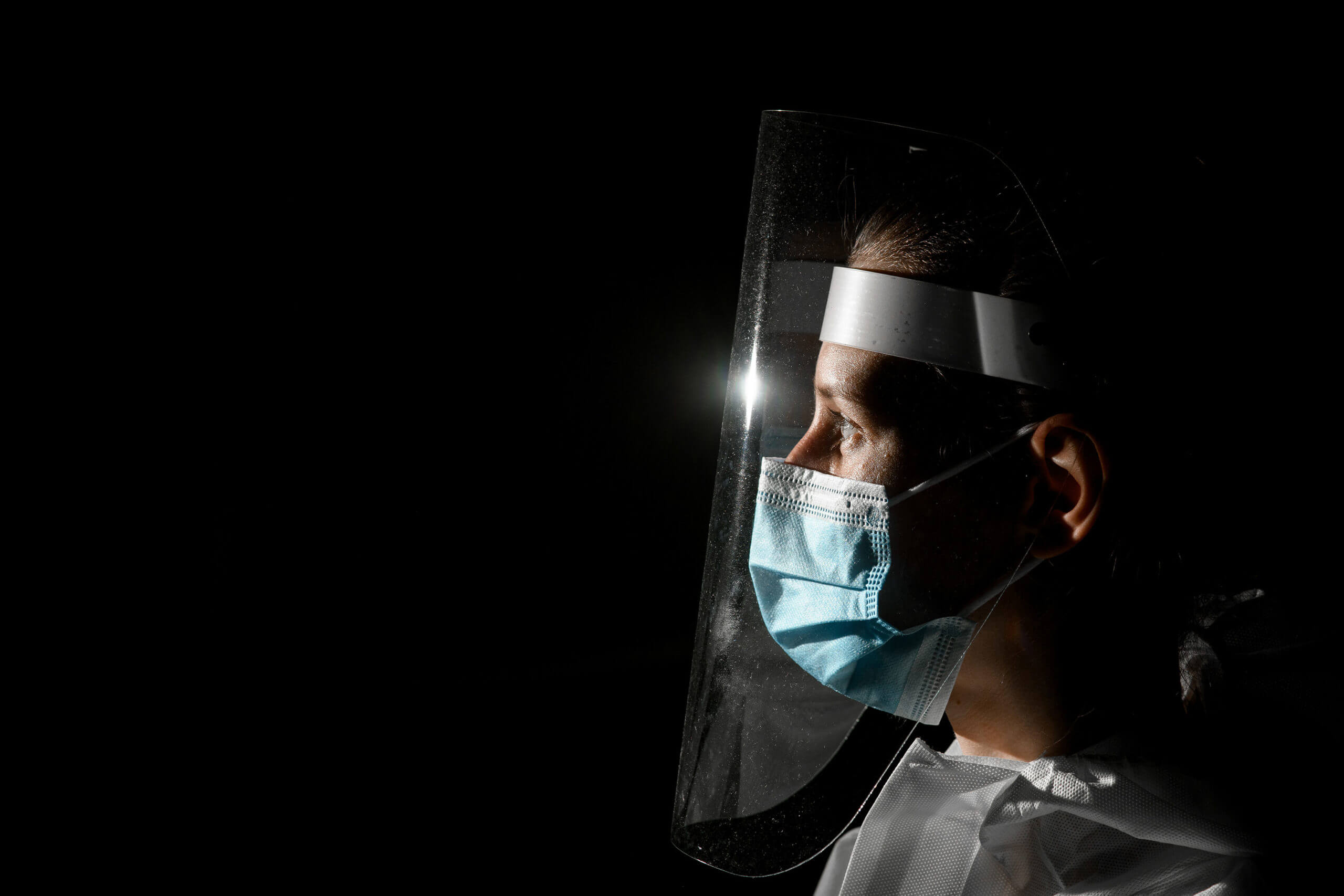 Dentist wearing full PPE with a black background