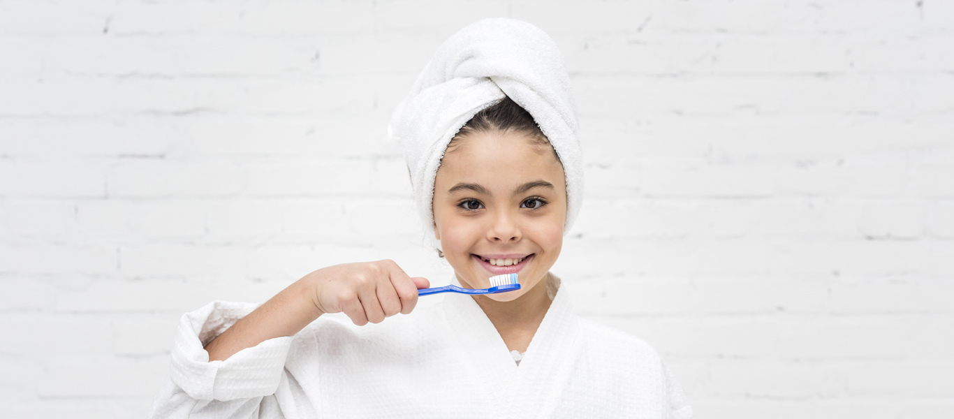 Young girl holding tooth brush while smiling at camera