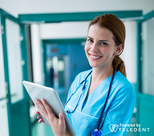 Dental assistant holding tablet and smiling at camera