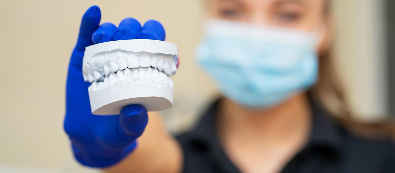 Dental assistant holding dental molds with blue gloves on