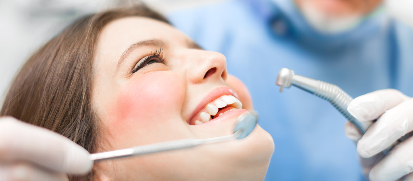 Dental patient smiling at dentist after teeth cleaning procedure is completed.